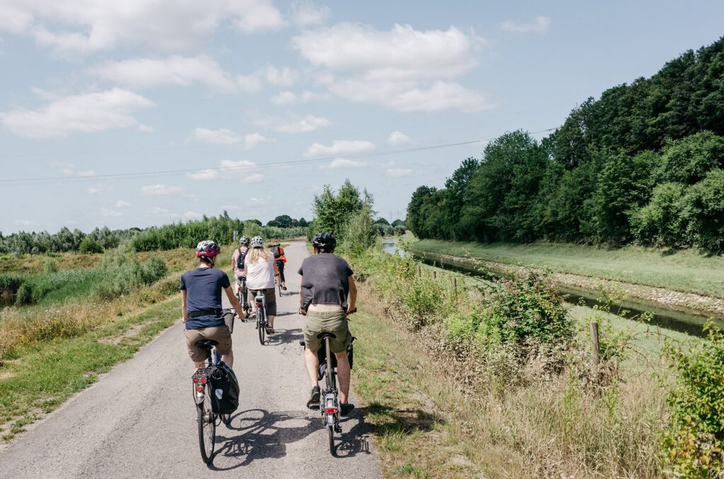Fahradfahrer:innen auf dem Emscher-Weg, umgeben von Natur, rechts die Emscher und Bäume